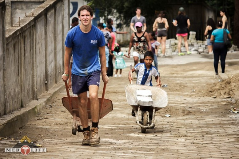 Volunteer and Boy Pushing Wheelbarrows
